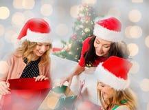 Счастливые женщины в шляпах santa с подарками рождества Стоковая Фотография RF