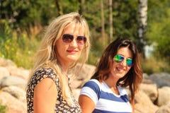 Счастливые женщины греют на солнце загорать и ослаблять на пляже Стоковое фото RF
