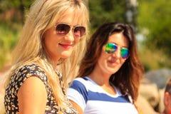 Счастливые женщины греют на солнце загорать и ослаблять на пляже Стоковые Изображения