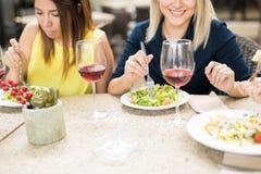 Счастливые женщины есть в ресторане Стоковая Фотография RF