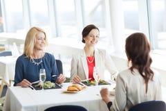 Счастливые женщины есть и говоря на ресторане Стоковая Фотография RF