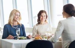 Счастливые женщины есть и говоря на ресторане Стоковые Фотографии RF