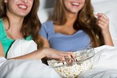Счастливые женщины есть попкорн и смотря ТВ дома Стоковое Фото