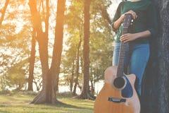 Счастливые женщины играя гитару в природе Стоковые Фото