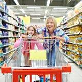 Счастливые женщины и девушка с покупками тележки Стоковые Изображения RF