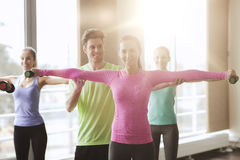 Счастливые женщины и тренер с гантелями в спортзале Стоковое Изображение RF