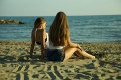 Счастливые женщины на пляже сидя и смотря заход солнца Стоковое Изображение