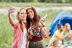 Счастливые женщины принимая selfie smartphone на располагаться лагерем Стоковые Изображения RF