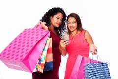 Счастливые женщины при хозяйственные сумки смотря телефон Стоковая Фотография