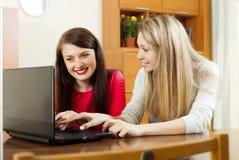 Счастливые женщины сидя на таблице с компьтер-книжкой Стоковые Изображения RF