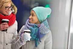 Счастливые женщины смотря один другого пока держащ устранимые чашки Стоковое Изображение