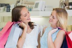 Счастливые женщины смотря один другого с хозяйственными сумками Стоковые Изображения