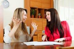 Счастливые женщины с документами на таблице i Стоковые Изображения