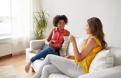 Счастливые женщины с домом gat питья говоря Стоковое Изображение RF