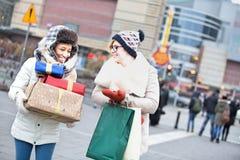 Счастливые женщины с подарками и хозяйственными сумками идя на улицу города во время зимы Стоковое Изображение RF