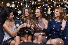 Счастливые женщины с стеклами шампанского на ночном клубе Стоковое Изображение
