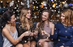Счастливые женщины с стеклами шампанского на ночном клубе Стоковые Фотографии RF