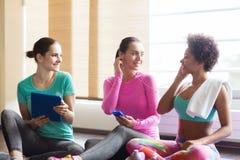 Счастливые женщины слушая к музыке в спортзале стоковые фото