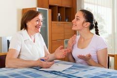 Счастливые женщины с финансовыми документами на таблице Стоковое Фото