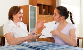 Счастливые женщины с финансовыми документами на таблице Стоковые Фото