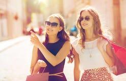 Счастливые женщины с хозяйственными сумками в городе Стоковое фото RF