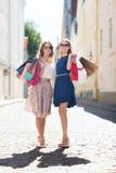 Счастливые женщины с хозяйственными сумками идя в город Стоковые Фото
