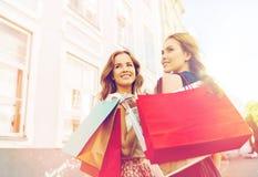 Счастливые женщины с хозяйственными сумками идя в город Стоковые Изображения