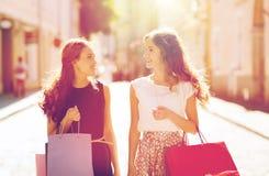 Счастливые женщины с хозяйственными сумками идя в город Стоковое Изображение RF