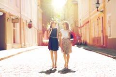 Счастливые женщины с хозяйственными сумками идя в город Стоковые Изображения RF