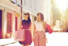Счастливые женщины с хозяйственными сумками идя в город Стоковое Фото
