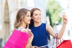Счастливые женщины с хозяйственными сумками и smartphone Стоковое Изображение RF