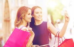 Счастливые женщины с хозяйственными сумками и smartphone Стоковая Фотография