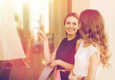 Счастливые женщины с хозяйственными сумками на окне магазина Стоковое фото RF