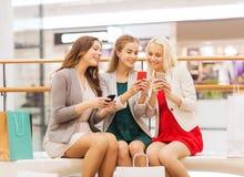 Счастливые женщины с smartphones и хозяйственными сумками Стоковая Фотография