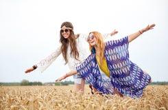 Счастливые женщины hippie имея потеху на поле хлопьев стоковое фото rf