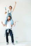 Счастливые жизнерадостные пары восстанавливая их стены дома совместно Стоковая Фотография