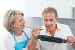 Счастливые зрелые пары варя еду в кухне стоковые изображения