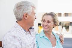 Счастливые зрелые пары сидя на стенде в городе Стоковое Фото