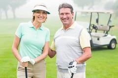 Счастливые играя в гольф пары с багги гольфа позади Стоковое Изображение