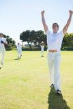 Счастливые игроки сверчка наслаждаясь победой пока стоящ на поле стоковое изображение