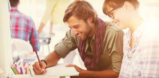 Счастливые дизайнеры работая на документе Стоковые Изображения