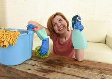 Счастливые и жизнерадостные таблица и мебель живущей комнаты женщины или домохозяйки очищая с тканью Стоковое Изображение RF