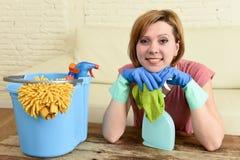 Счастливые и жизнерадостные таблица и мебель живущей комнаты женщины или домохозяйки очищая с тканью Стоковая Фотография