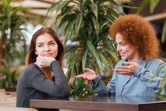 Счастливые и унылые молодые женщины говоря в кафе стоковое изображение