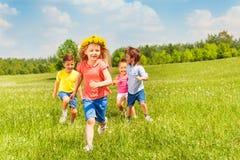 Счастливые идущие дети в зеленом поле во время лета Стоковая Фотография RF