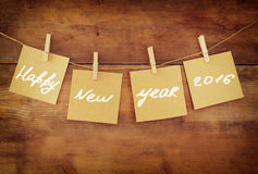 Счастливые карточки Нового Года висят на штыре одежд над деревянной предпосылкой Стоковая Фотография RF