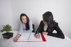 Счастливые коммерсантки работая на столе в офисе Стоковая Фотография