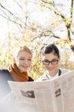 Счастливые коммерсантки читая газету на парке Стоковые Фото
