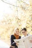 Счастливые коммерсантки читая газету совместно на парке Стоковые Фото