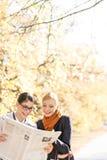 Счастливые коммерсантки читая газету совместно на парке Стоковые Изображения RF